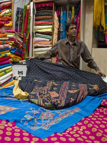 A seller displaying cloth items at Mangaldas Market.